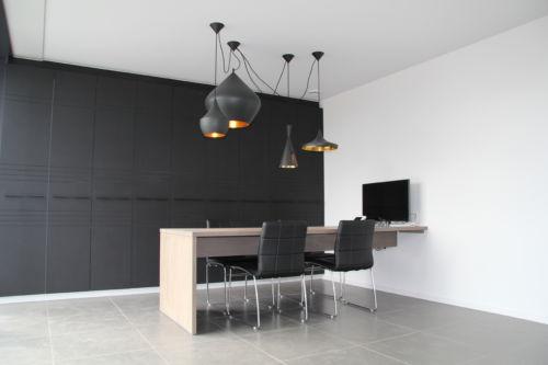 bureau met zwarte kanstenwand en fineer