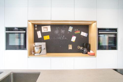 Houten nis in strakke keuken met krijt en magneetbord