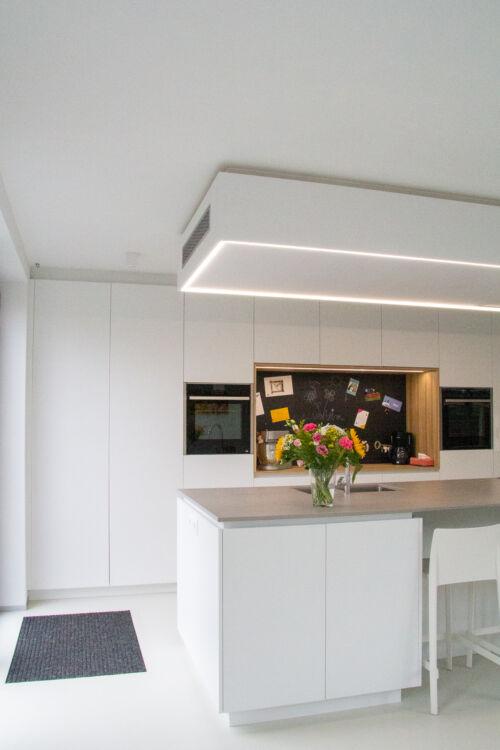 Strakke witte keuken met grijze dekton
