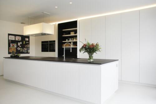strakke witte keuken met zwart werkblad
