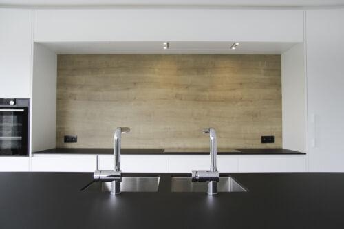 witte laminaten keuken met een zwart dekton werkblad en houten accenten
